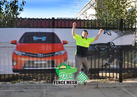 Printed car on a banner attached to a fence for signage